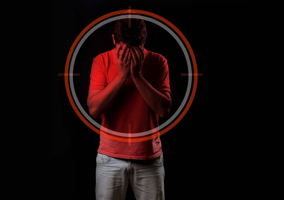 Man in Crosshairs covering up his face with hands