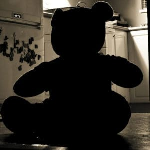 Teddy Bear blacked in a well lit Kitchen